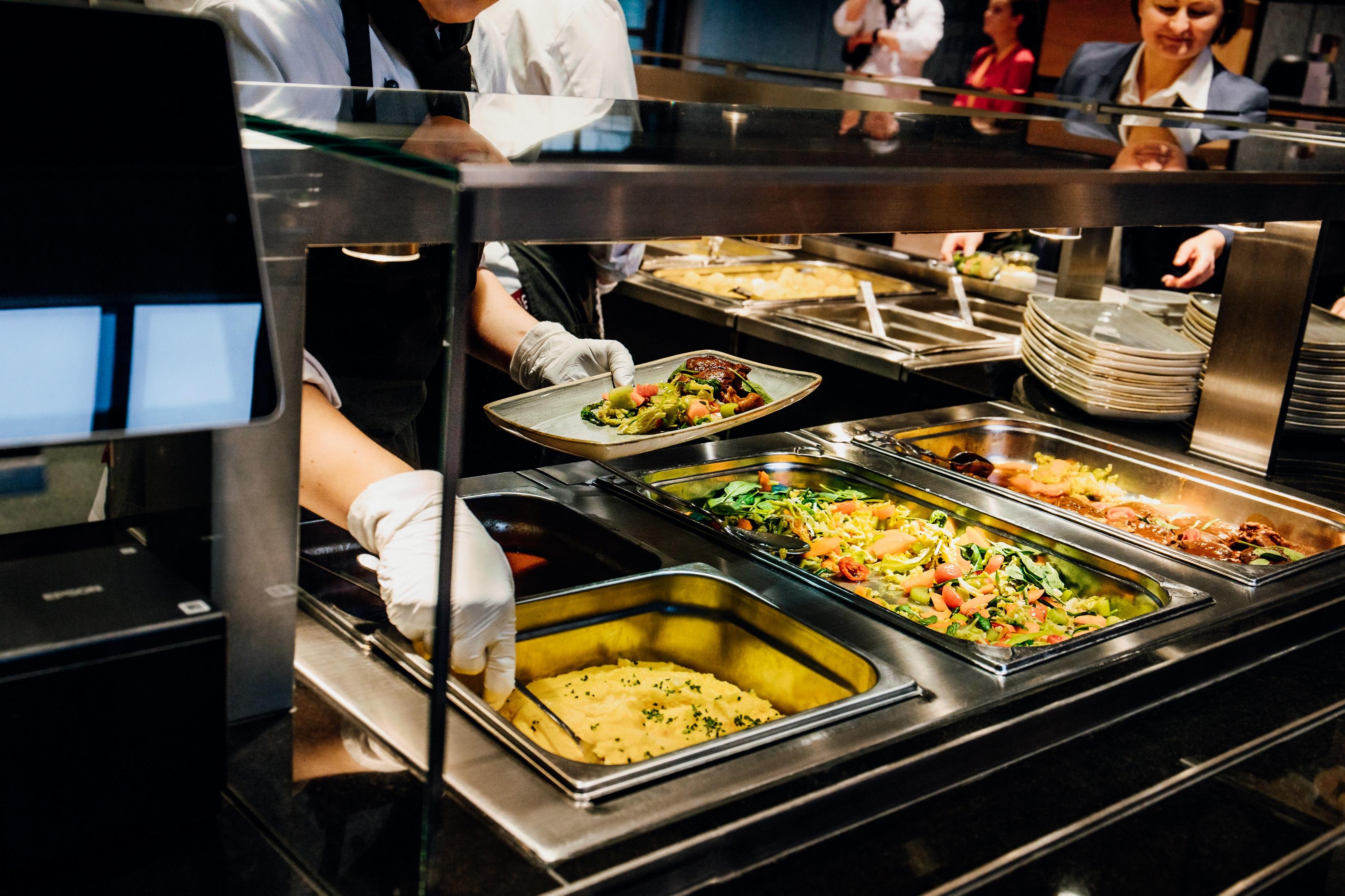 Essensausgabe einer Kantine mit verschiedenen Speisen in der Auslage